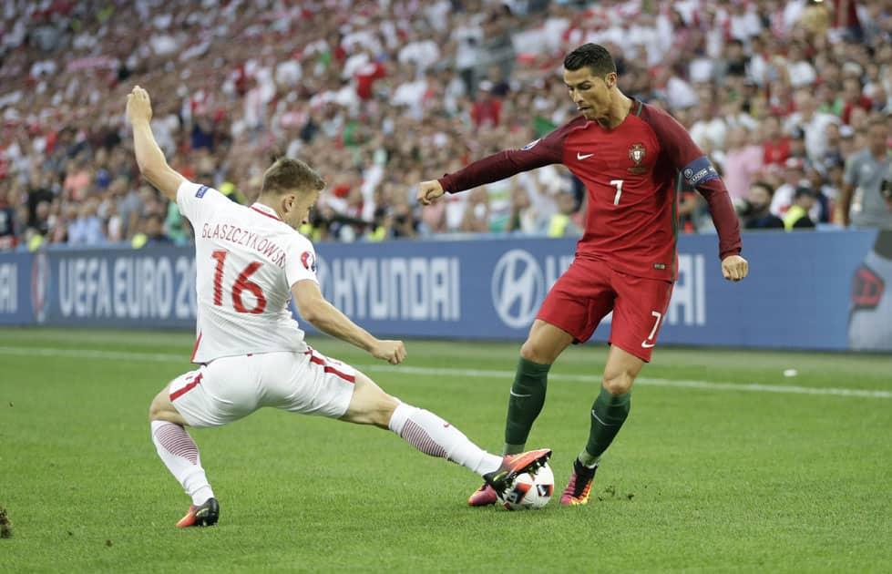 Cristiano Ronaldo, right, is tackled by Poland's Jakub Blaszczykowski