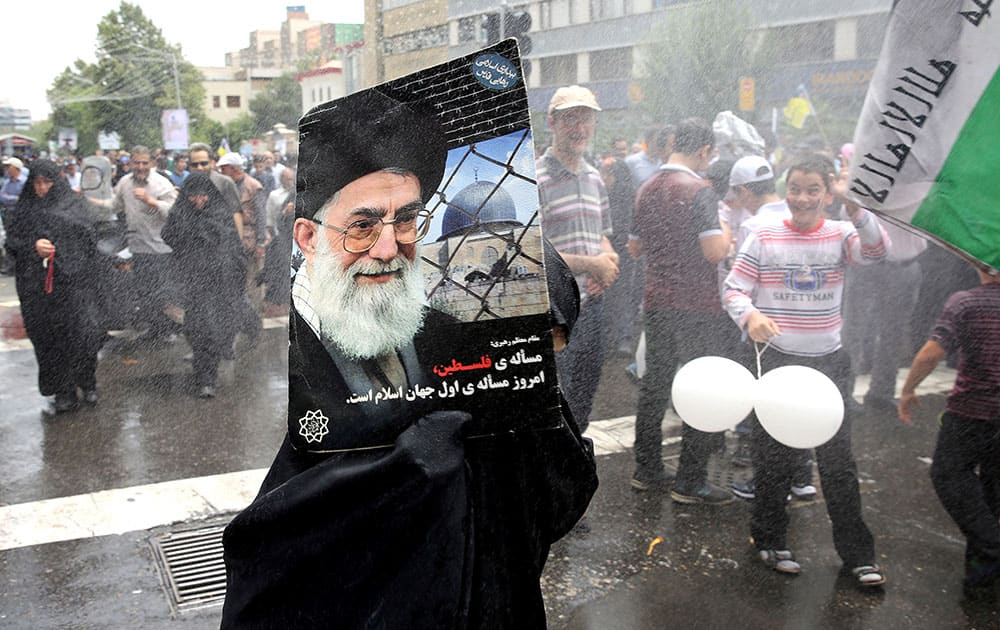 An Iranian demonstrator holds a poster showing Iranian Supreme Leader Ayatollah Ali Khamenei