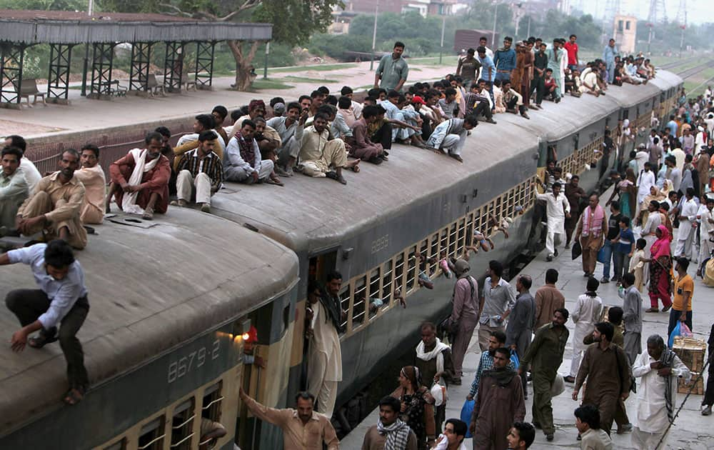 People ride on a crowded passenger train to celebrate upcoming Eid al-Fitr