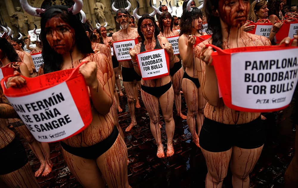 People cover their bodies with theatrical blood as they hold buckets with slogans to protest against bull runs