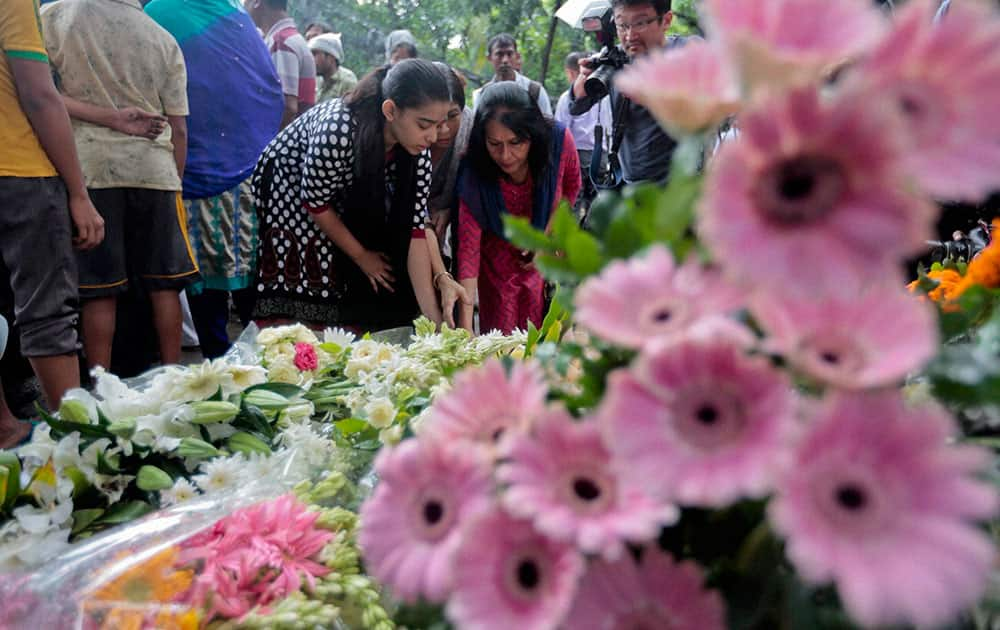 People offer flowers to pay their respects to the victims of the attack on Holey Artisan Bakery, in Dhaka
