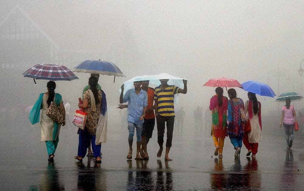 Tourists trying to protect themselves during heavy rainfall in Shimla.