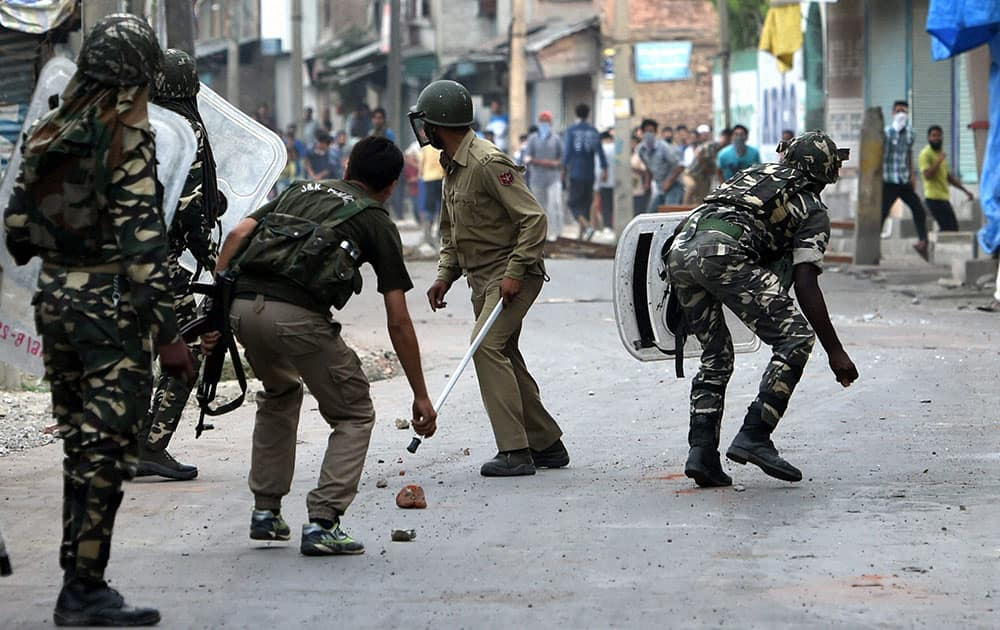 Security jawans chashing away stone throwing youths during a clash in Srinagar.