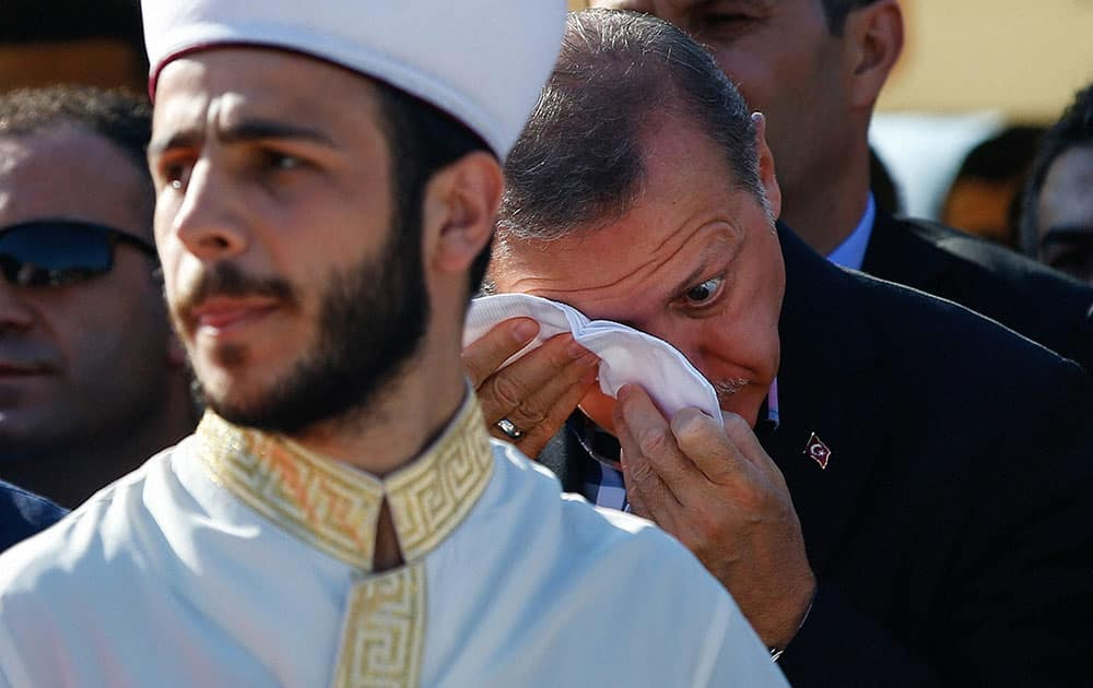 Turkish President Recep Tayyip Erdogan weeps during the funeral of Mustafa Cambaz, Erol and Abdullah Olcak in Istanbul