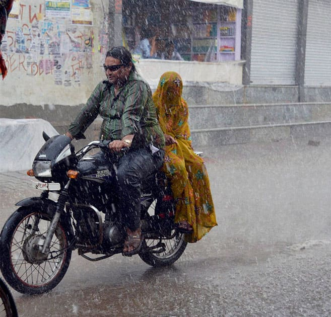 A couple rides a motorcycle in heavy rains in Mathura