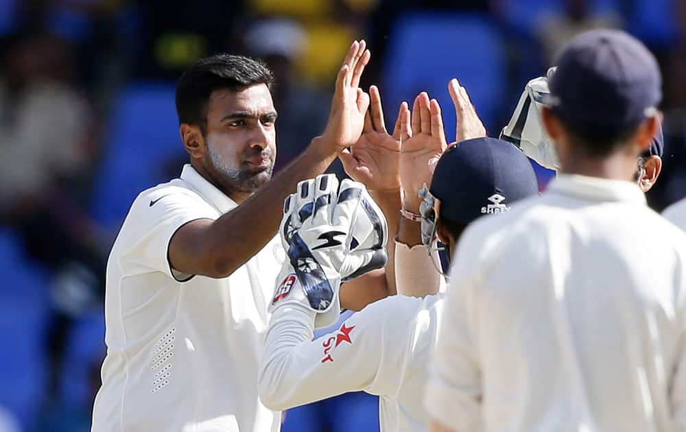 Ravichandran Ashwin  is congratulated by teammates after dismissing Devendra Bishoo