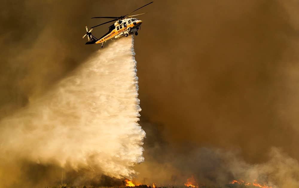 A helicopter makes a drop on a wildfire near Placenta Caynon Road in Santa Clarita, Calif.