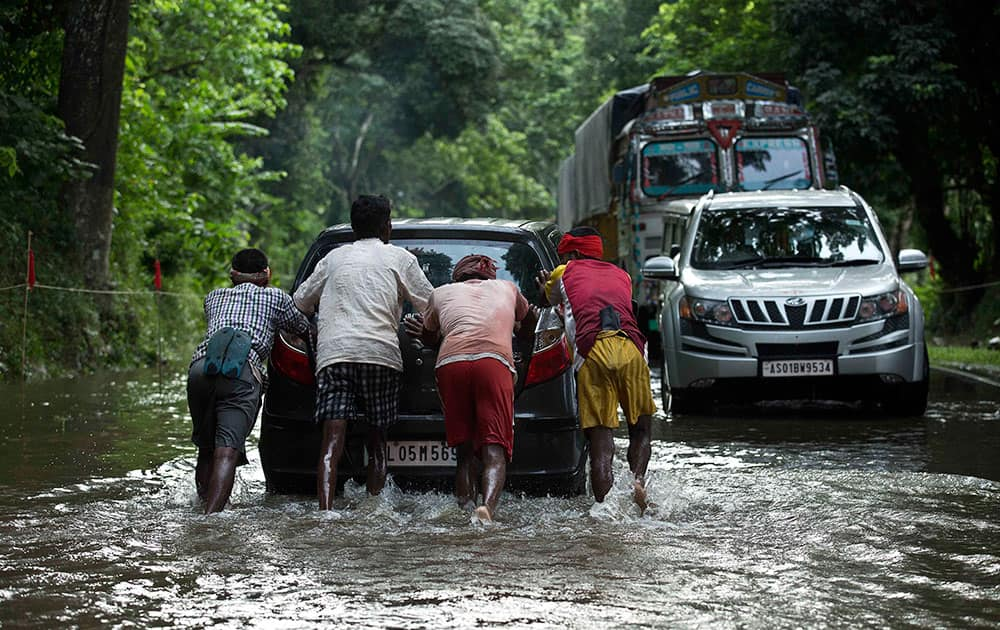 People push a vehicle to help commuters cross a flooded highway in Kaziranga National Park
