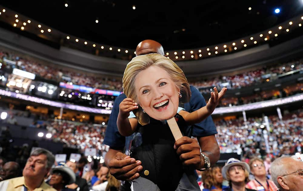 Ethan Jennings grabs a cardboard cutout of the face of Democratic Presidential candidate Hillary Clinton