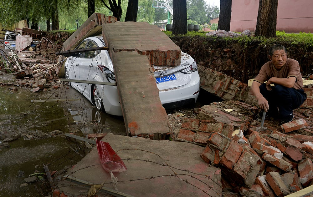 A man takes a rest near damaged vehicles following a flood in Shenyang in northeast China's Liaoning province
