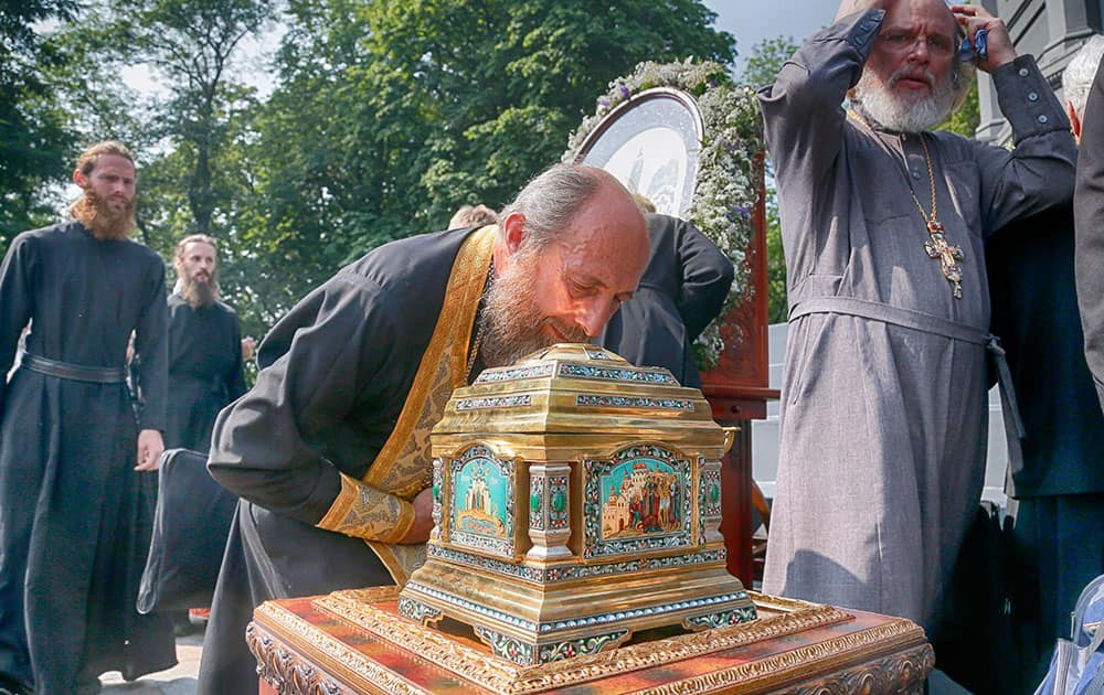 Orthodox clergyman kisses the relics at a prayer ceremony in downtown Kiev
