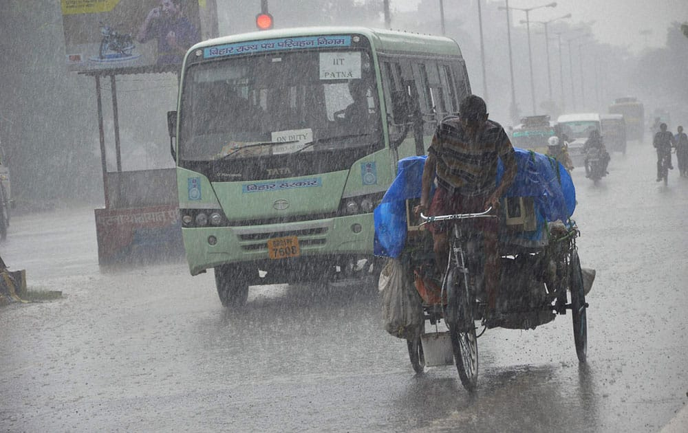 People moves during heavy Monsoon rain in Patna