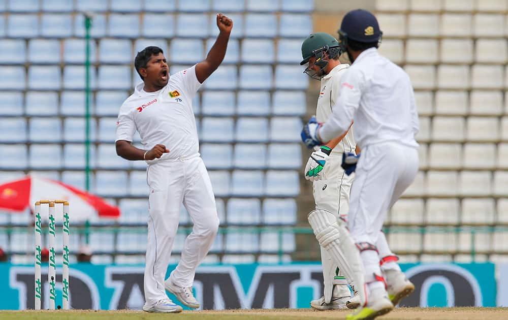 Rangana Herath celebrates the wicket of Australia's David Warner