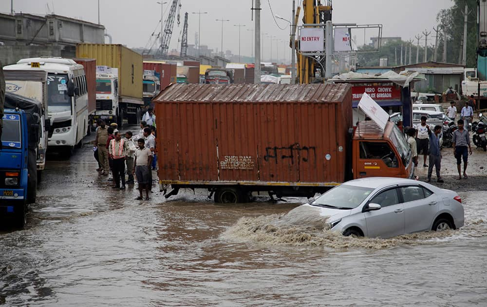 A car navigates its way through a flooded street after heavy rainfall in Gurgaon