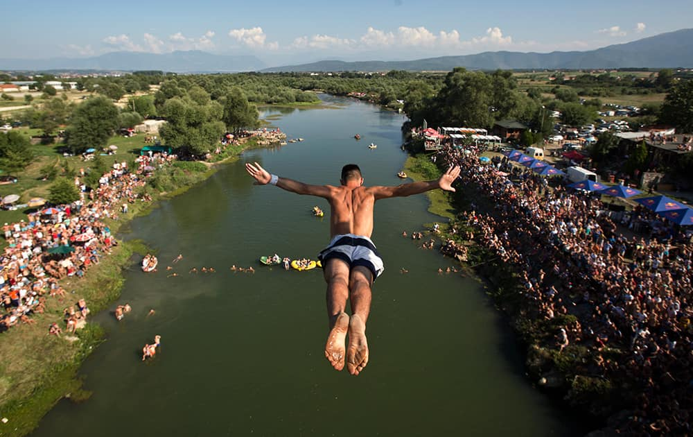 Spectators watch from the river banks as a diver launches from the Ura e Shenjte bridge