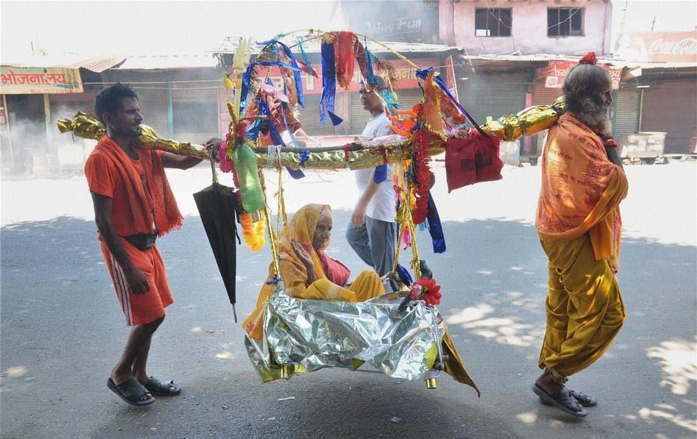 Devotees carrying a woman in a Kanwar in Meerut.