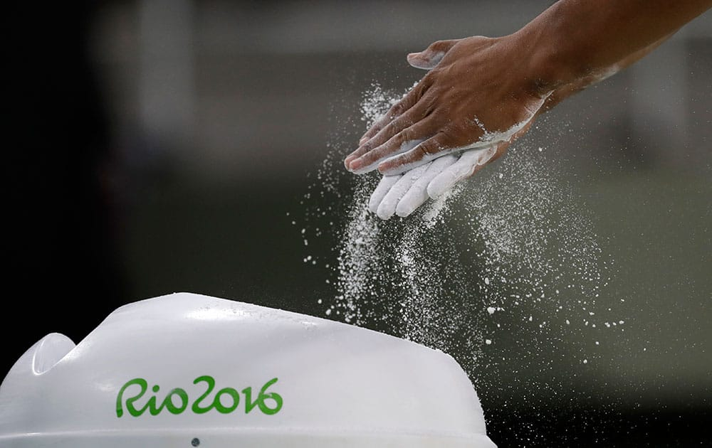 Gymnast Marios Georgiou from Cyprus rubs chalk on his hand before performing on an apparatus ahead of the 2016 Summer Olympics in Rio de Janeiro, Brazil