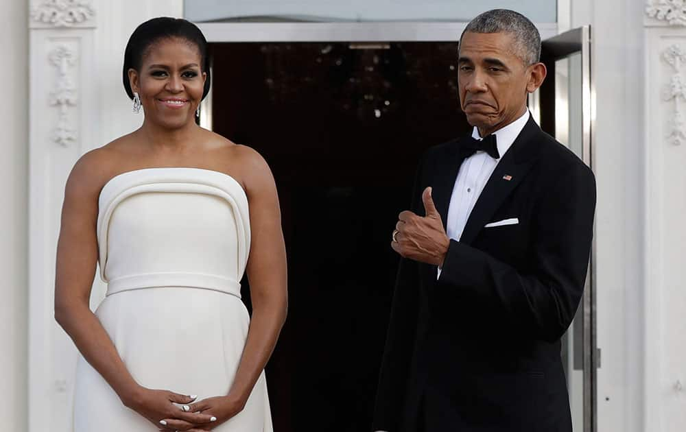 President Barack Obama flashes a thumbs up after gesturing toward first lady Michelle Obama, as they wait for Singapore's Prime Minister Lee Hsien Loong