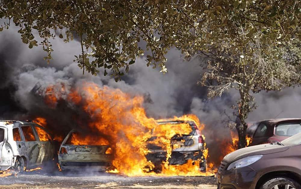 Cars burn in a parking lot in Barragem da Povoa eastern Portugal