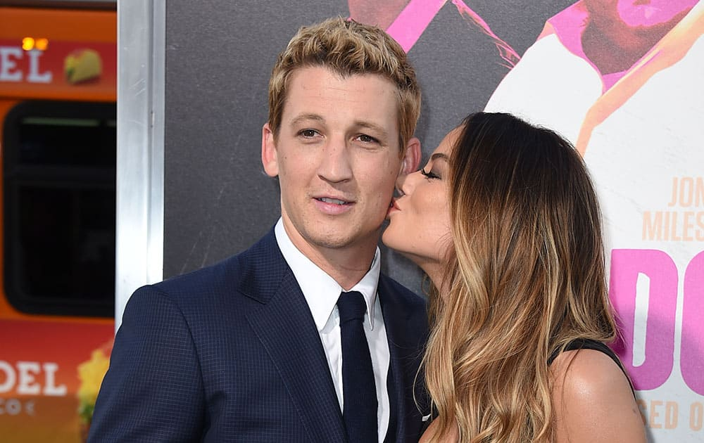 Keleigh Sperry, right, kisses Miles Teller as they arrive at the Los Angeles premiere of