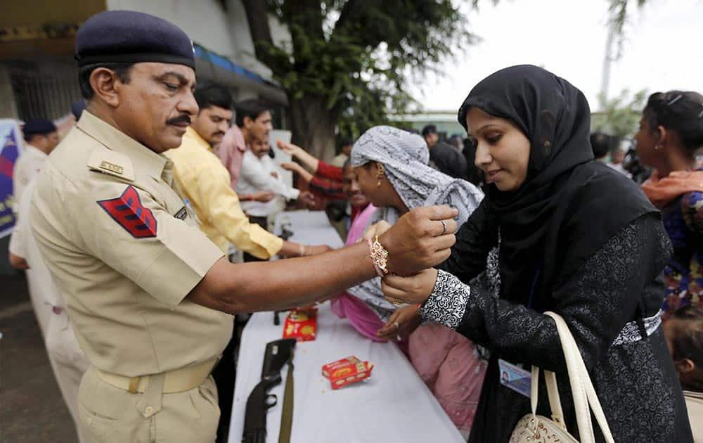 Muslim women tying Rakhi
