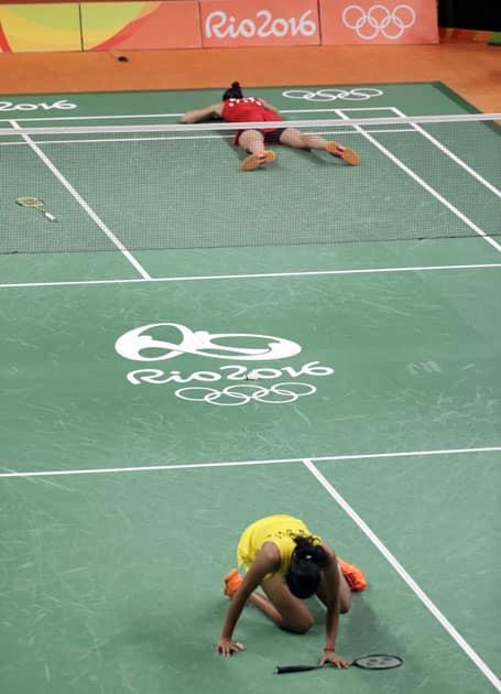 Spain's Carolina Marin, top, lies on the court