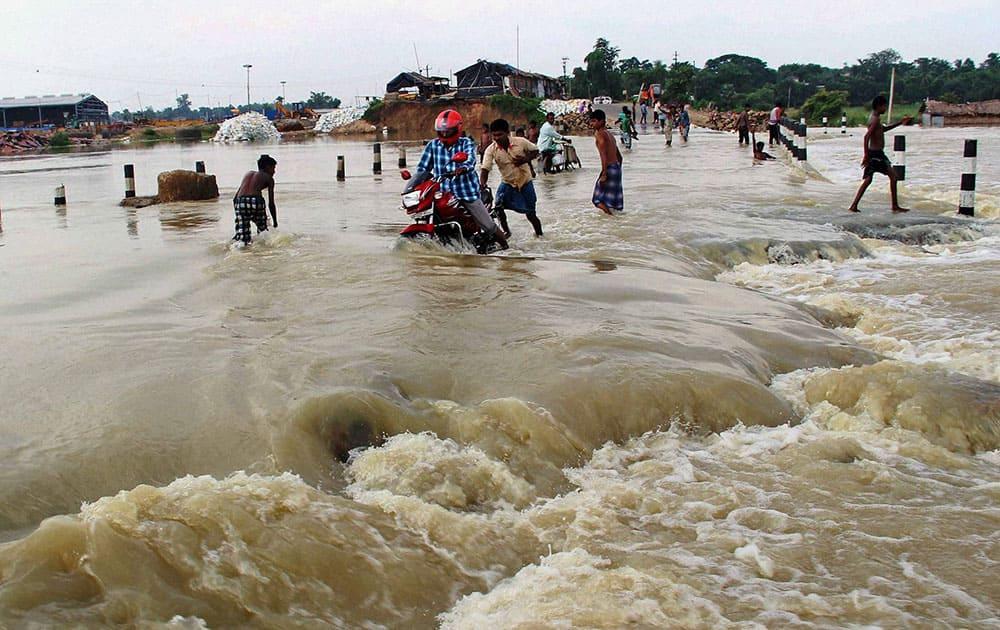 Villagers wade though the flooded Burdwan-Katwa road at Norjai Setu in Burdwan district of West Bengal