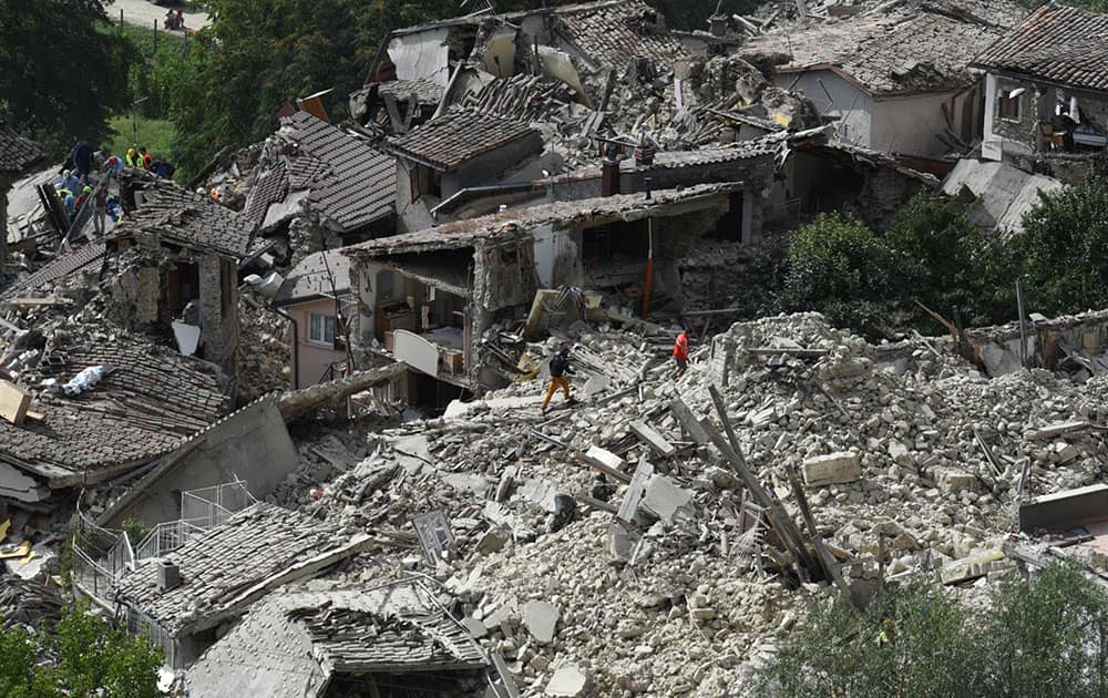 Rescuers are seen working in the rubble of collapsed and damaged houses in the village of Pescara del Tronto, central Italy