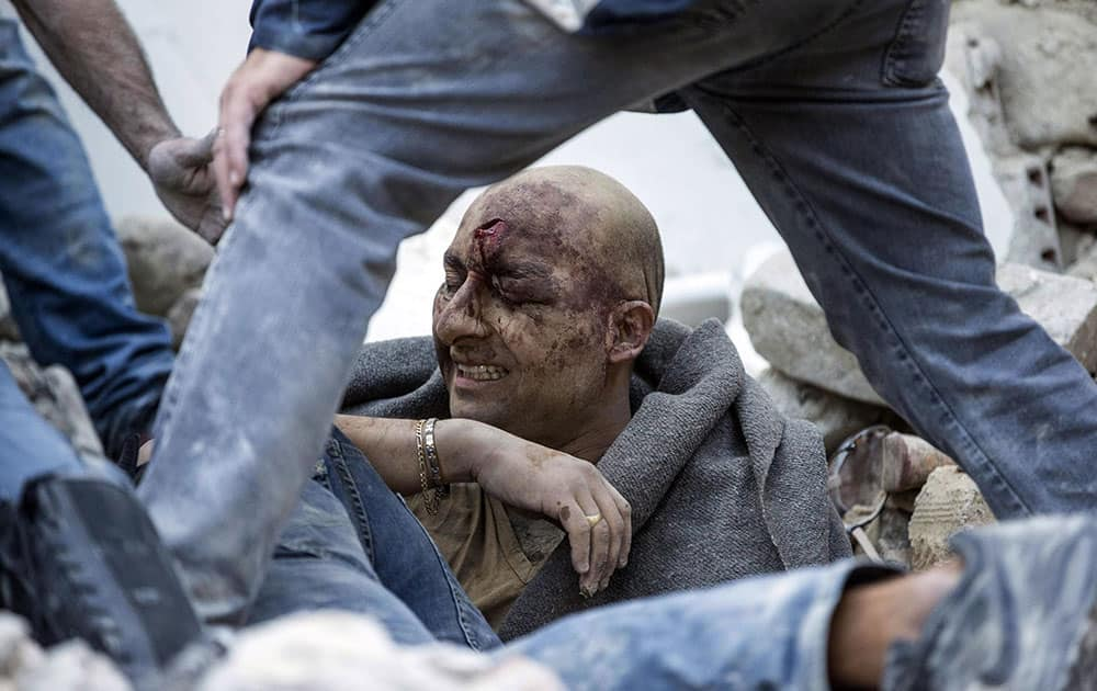 A man is pulled out of the rubble following an earthquake in Amatrice Italy