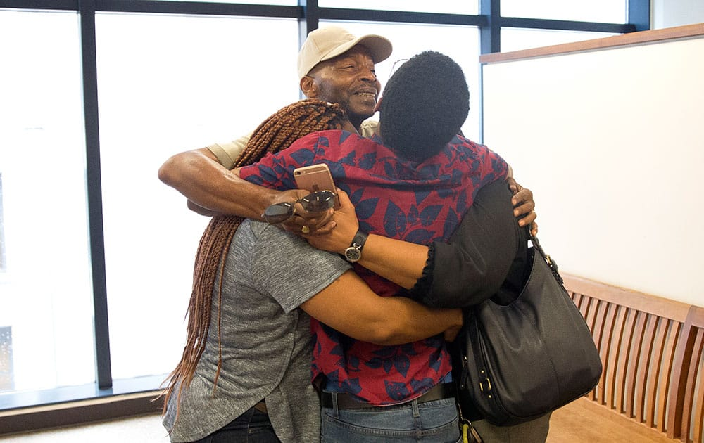 Marquez Tolbert hugs his family including his grandfather Johnny Tolbert after a trial for Martin Blackwell in Atlanta