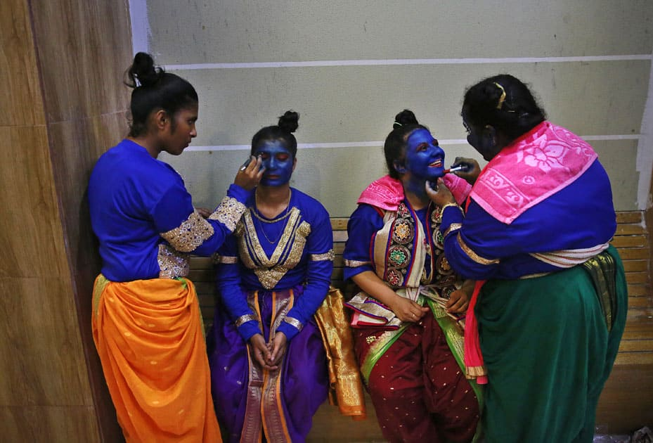 Indian students get their faces painted in blue color