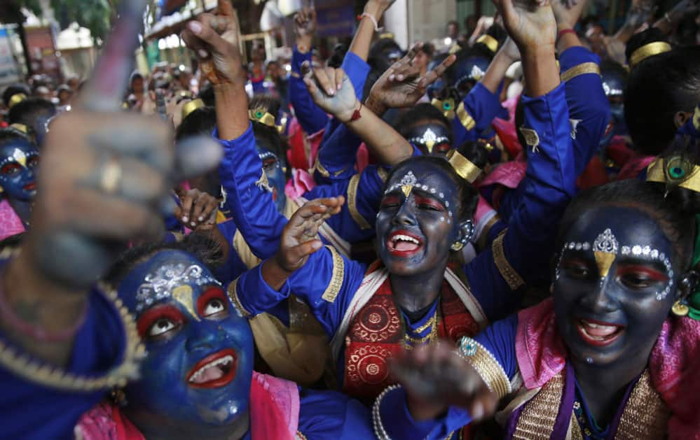 faces painted in blue color cheer during Janmashtami