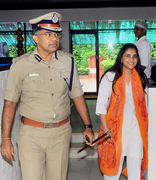 City police commissioner N Chandrasekhar escorts Kannada actor and Congress member Ramya as she comes out of a hotel after attending a discussion