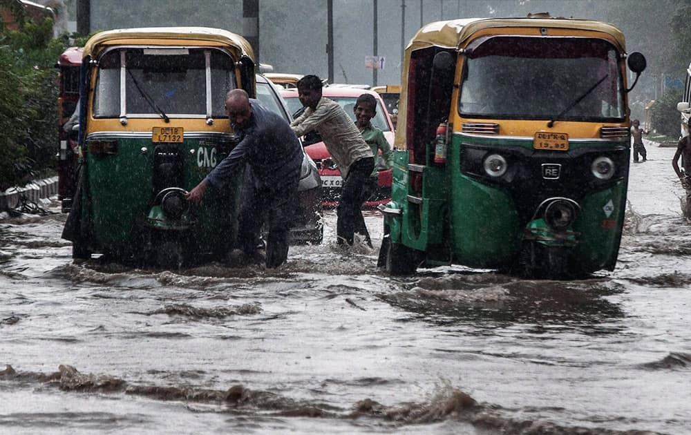 Vehicles make their way through floodwaters on a street after heavy rainfall in New Delhi