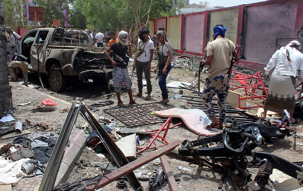 Fighters loyal to the government gather at the site of a suicide car bombing in Yemen' a southern city of Aden, Yemen