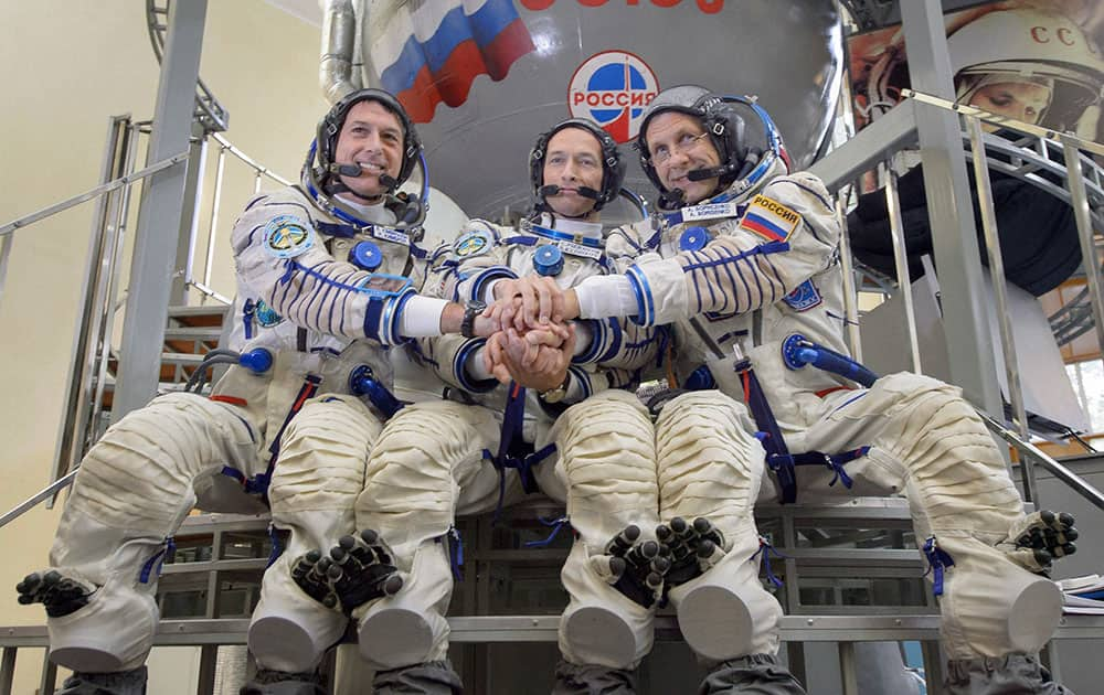 astronaut Shane Kimbrough and Russian cosmonauts Sergey Ryzhikov and Andrey Borisenko pose in front of Russian Soyuz space craft simulator during their final pre-flight training session