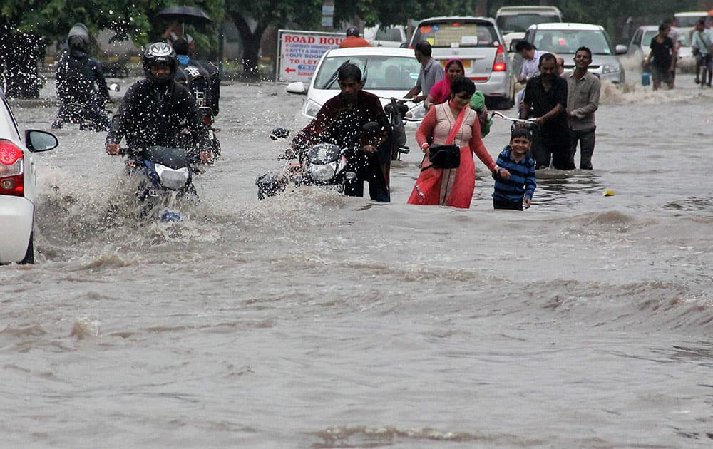 people make their way through floodwaters on a street during heavy rainfall in Gurgaon
