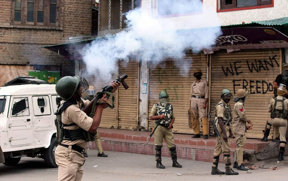 Security jawans fire tear gas shells to disperse protesters who staged a protest march towards Lal Chowk