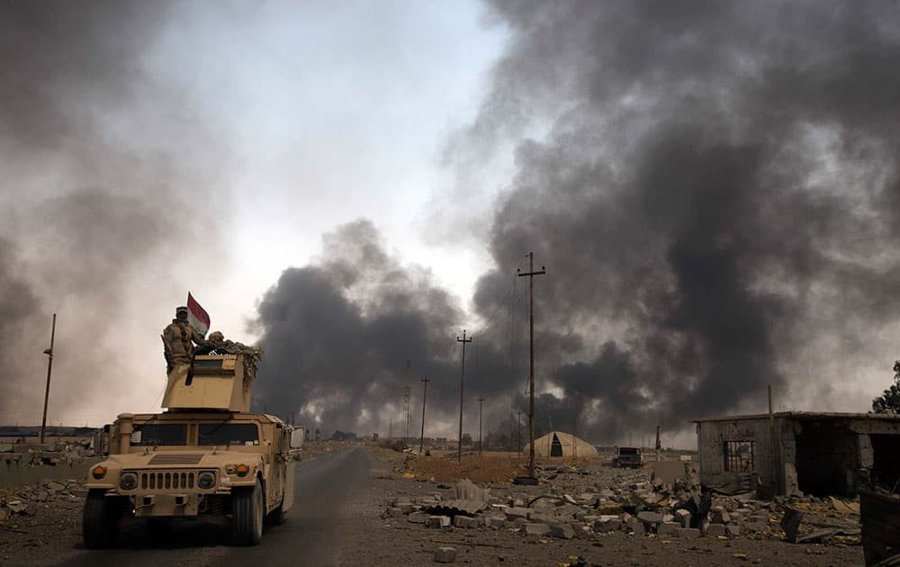 Iraqi security forces patrol as smoke rises from burning oil wells in Qayara