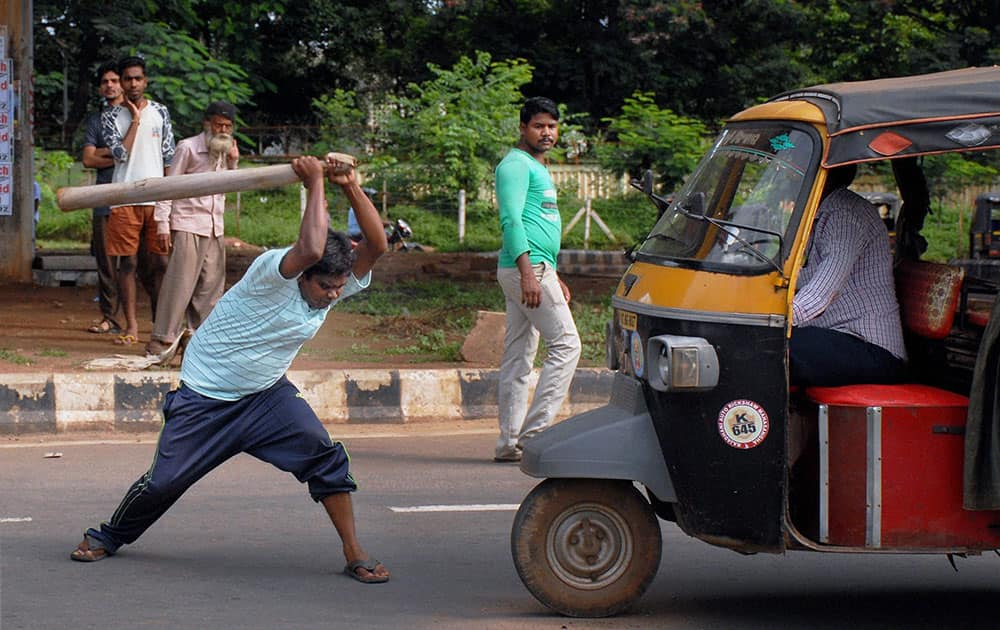 A protester halts an auto during All India Strike called by Left parties and Trade unions in Bhubaneswar