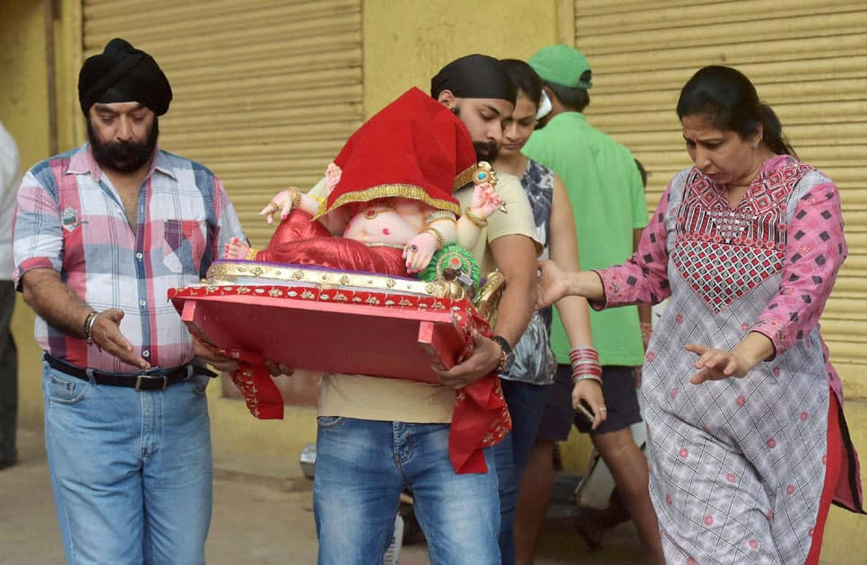 Punjabi community carries an idol of Lord Ganesh