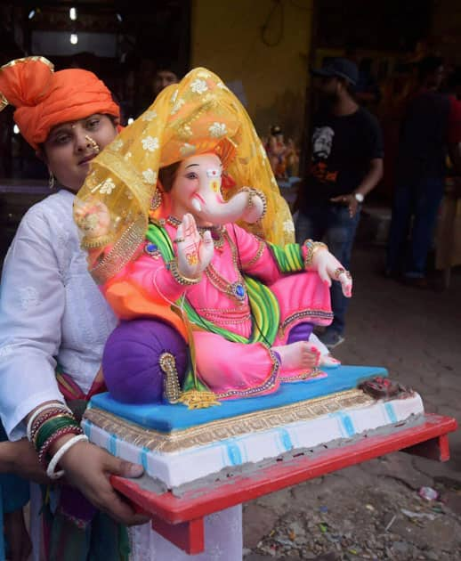 A woman carries an idol of Lord Ganesh