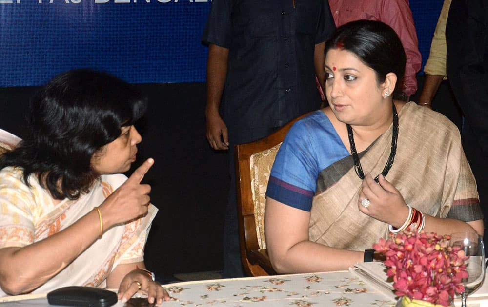 Union Textiles Minister Smriti Irani talks with Textile Secretary Rashmi Verma (L) during inauguration of Jute Sector Shakehoders meeting in Kolkata
