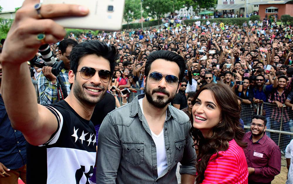 Gaurav Arora (L), Emraan Hashmi and Kriti Kharbanda take a selfie with their fans during a promotional event of their upcoming film Raaz Reboot at a college in Ahmedabad