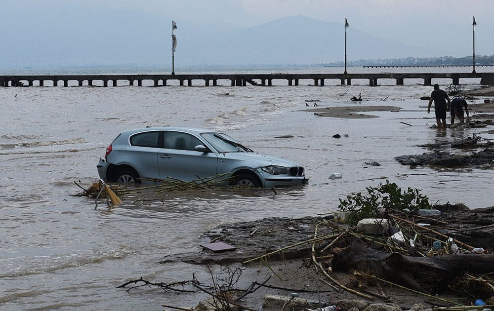A car is abandoned in the sea in Agia Triada village about 20 kilometers from the city of Thessaloniki, northern Greece, after heavy overnight rain