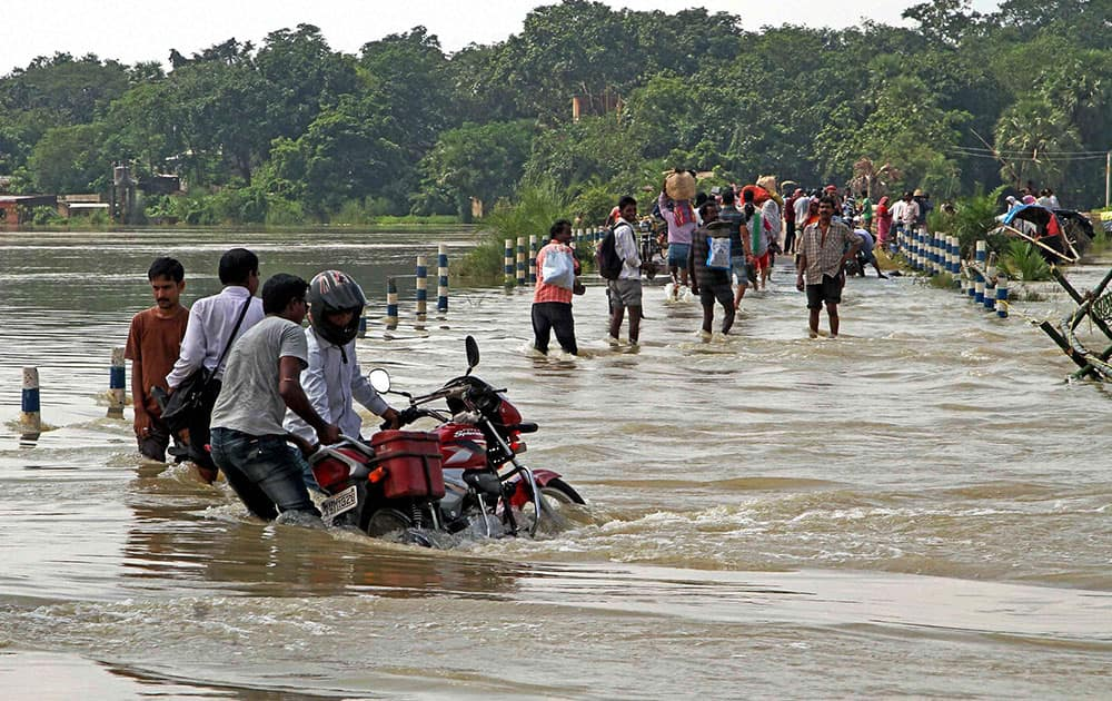 Villagers risk their lives as they cross the flooded Kunye river at Laghata in Birbhum district of West-Bengal