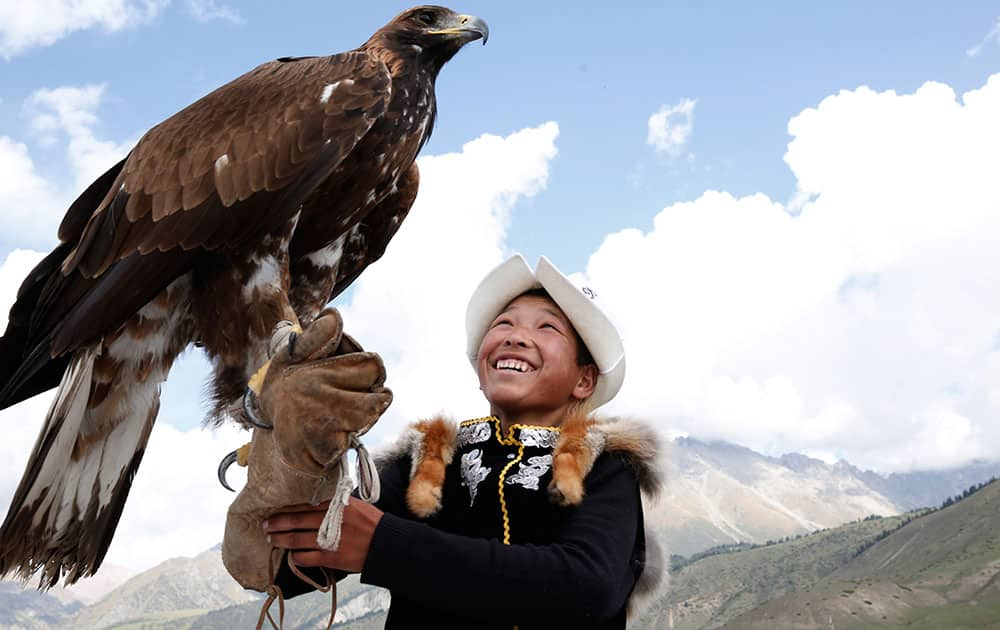 A boy handles an eagle at the World Nomad Games