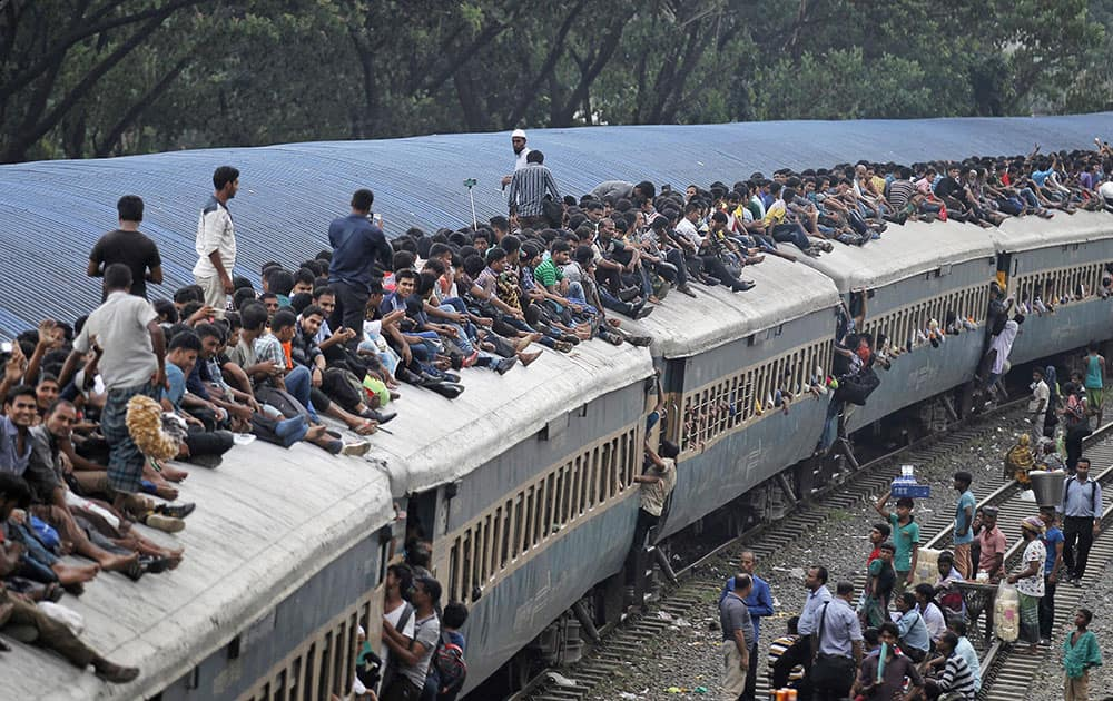 Bangladeshi Muslims travel on the roof of an overcrowded train as they head to their hometowns ahead of Eid al-Adha