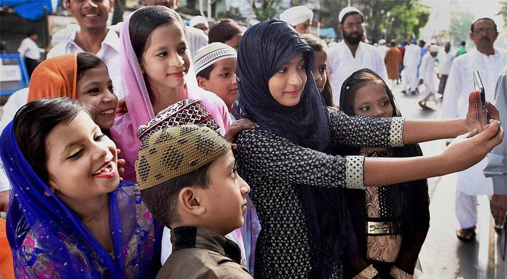 Children take selfies during Eid al-Adha