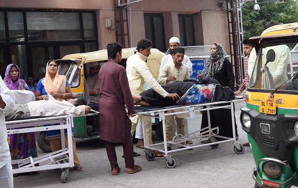 Patients suffering from fever being carried on stretchers outside RML hospital in New Delhi